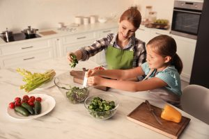 Mother,And,Daughter,Cooking,Salad,Together,In,Kitchen